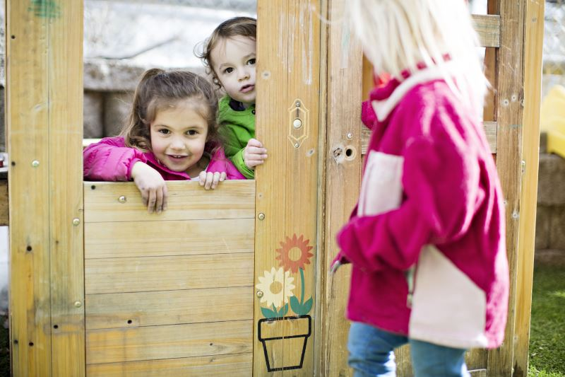 A group of children behind a small wooden gate