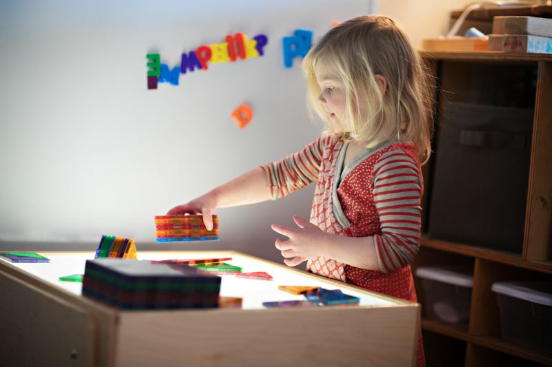 A girl playing in an early childhood center classroom