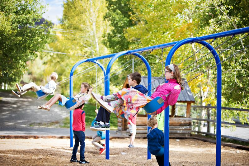 Students swinging on a swing-set and playing in a playground
