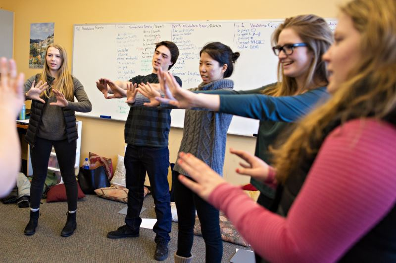 A group of students in a circle extending their arms in a classroom