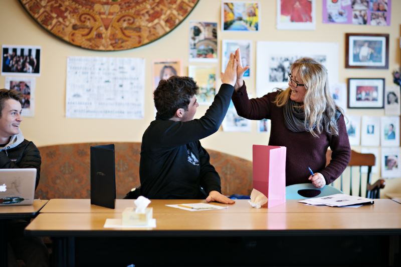 A teacher and student high five at a table in class