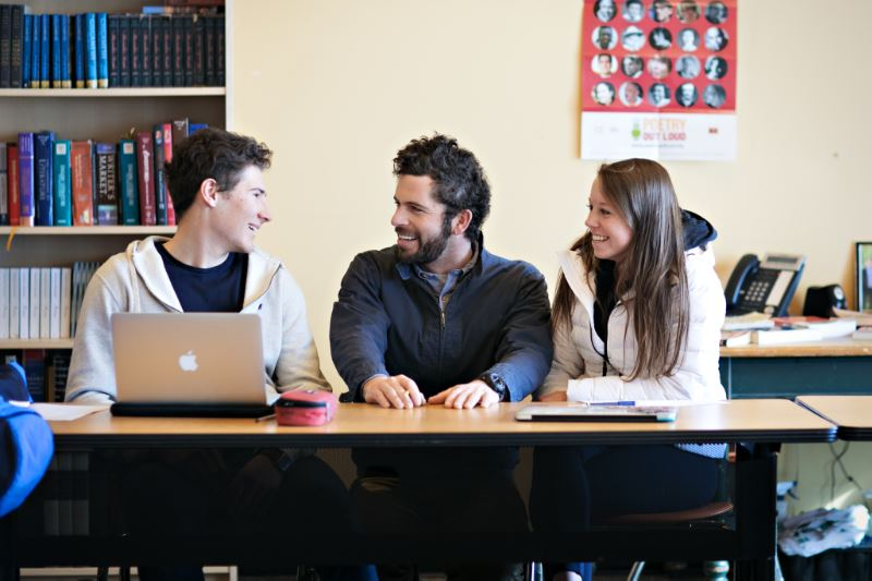 Three people sitting at a table in a classroom