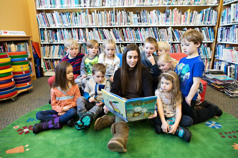 A teacher reading to a group of children in a library