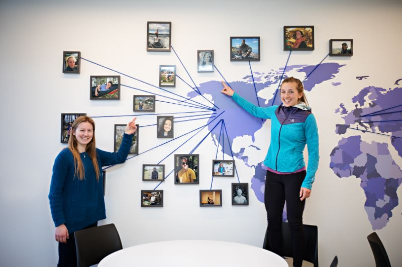 Students pointing to a map of the country on a wall