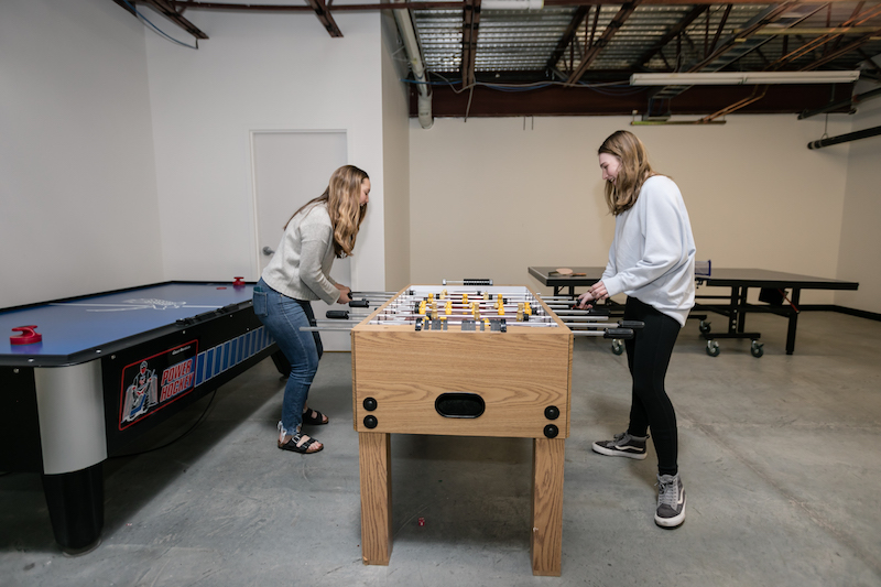 Two students playing Foosball in a game room