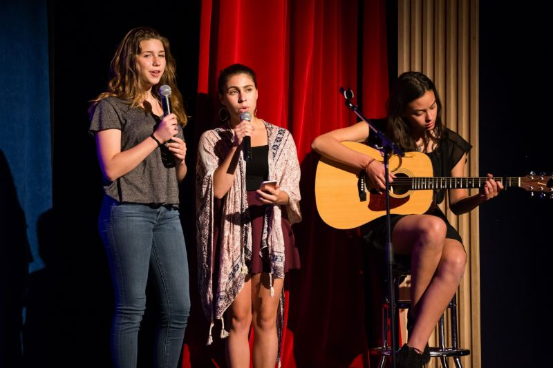 Three girls on stage as part of a musical group