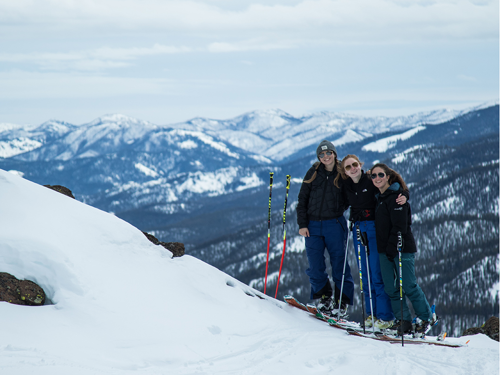Three students standing on a ski mountain