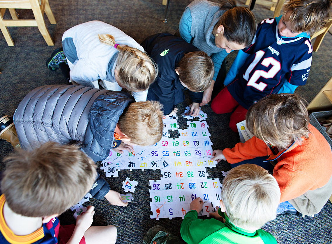 Students working on a puzzle in their elementary class