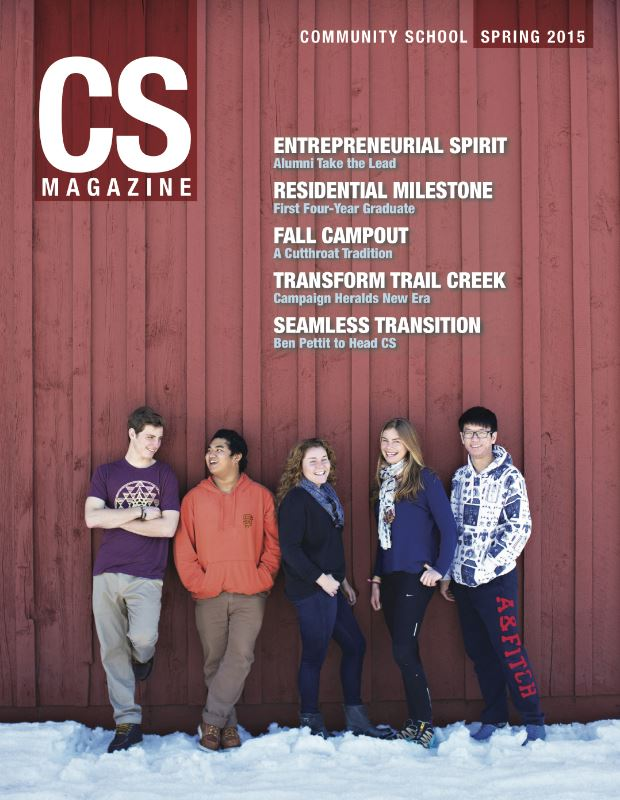 CS magazine of five students in front of a red wooden wall