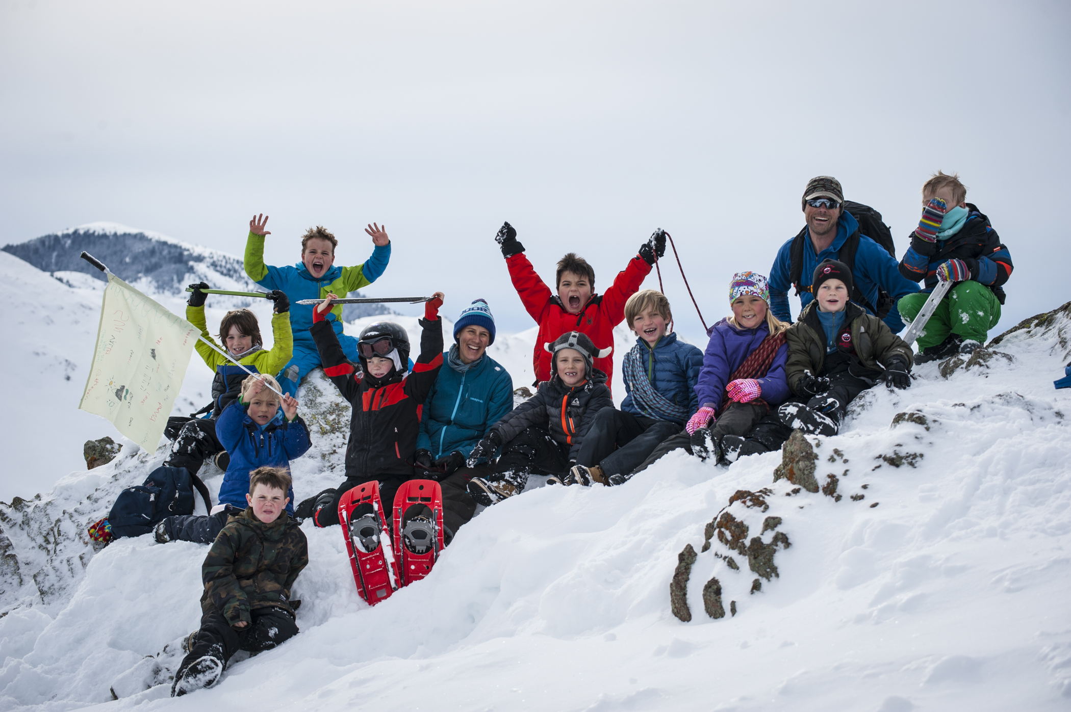 A group of students sitting on a snowy mountain