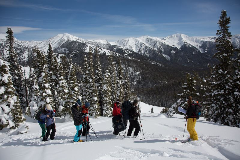 A group of skiers standing on a snowy mountain slope