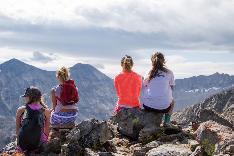 Four students sitting on a mountain looking out over the valley