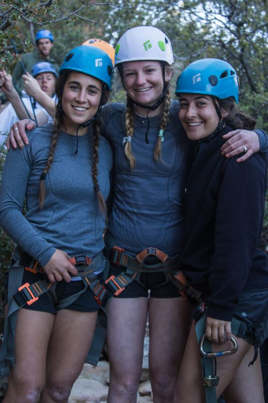 A group of students in helmets and climbing gear