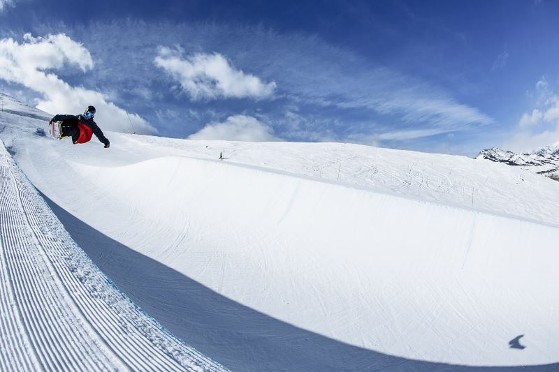 A snowboarder training in a halfpipe
