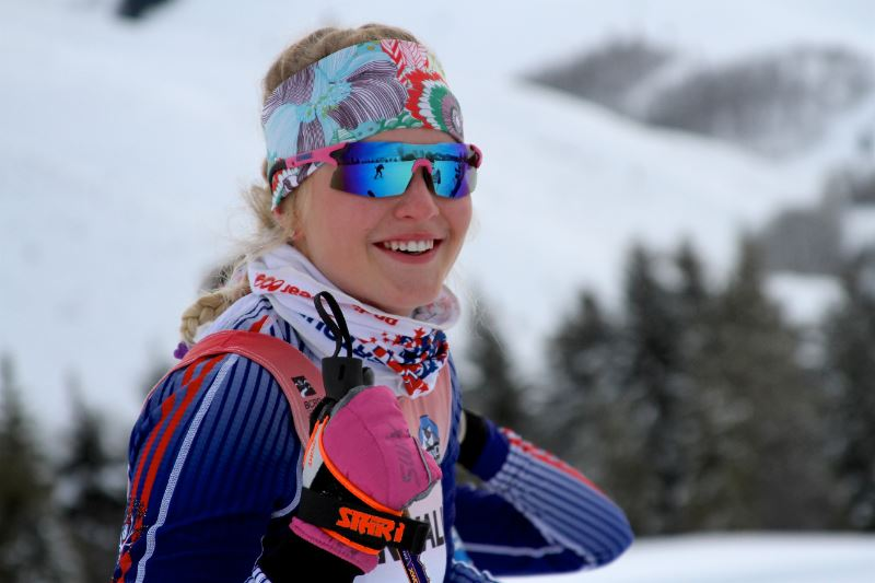 A smiling girl outfitted in ski gear