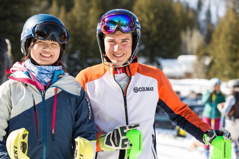Two smiling people in ski gear on a ski trail