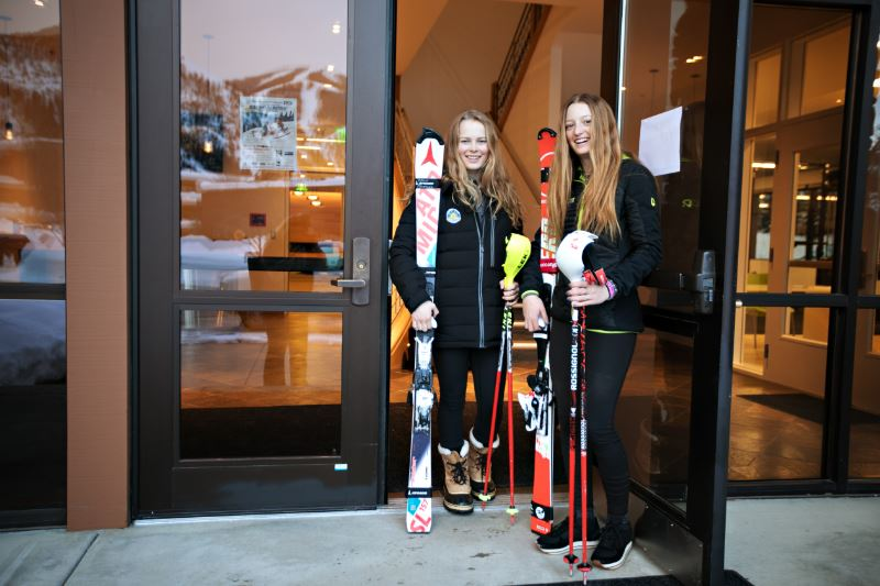 Two girls with their skis standing in a doorway