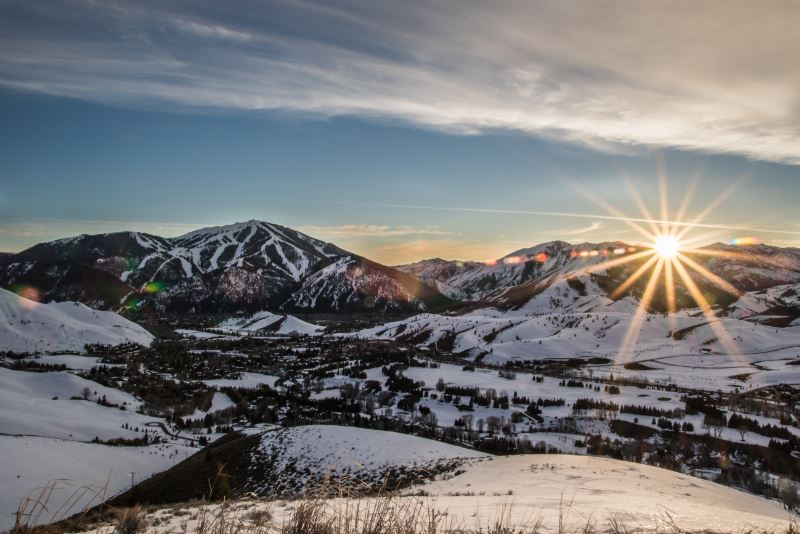 A sun rising over the snowy Rocky Mountains