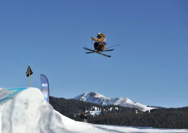 A skier in mid-air on a ski slope