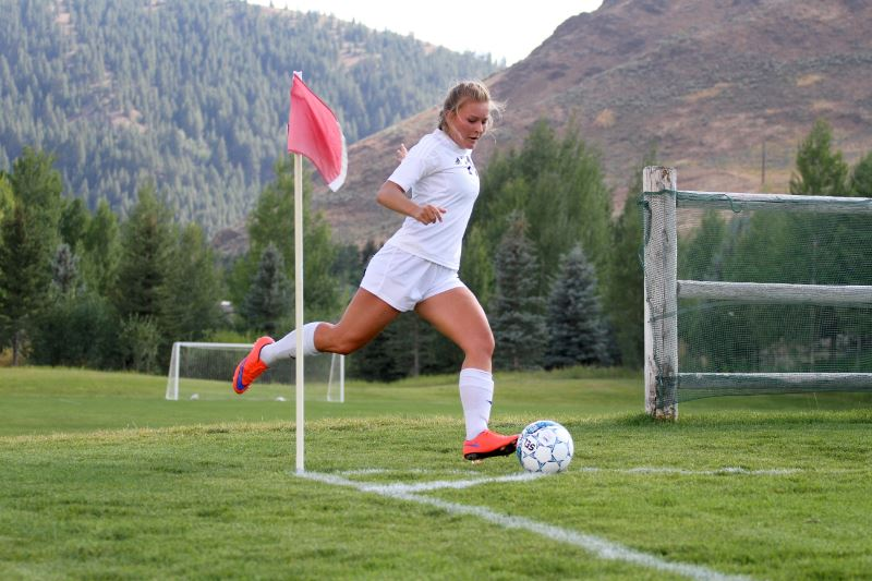 A girl taking a corner kick during a soccer game