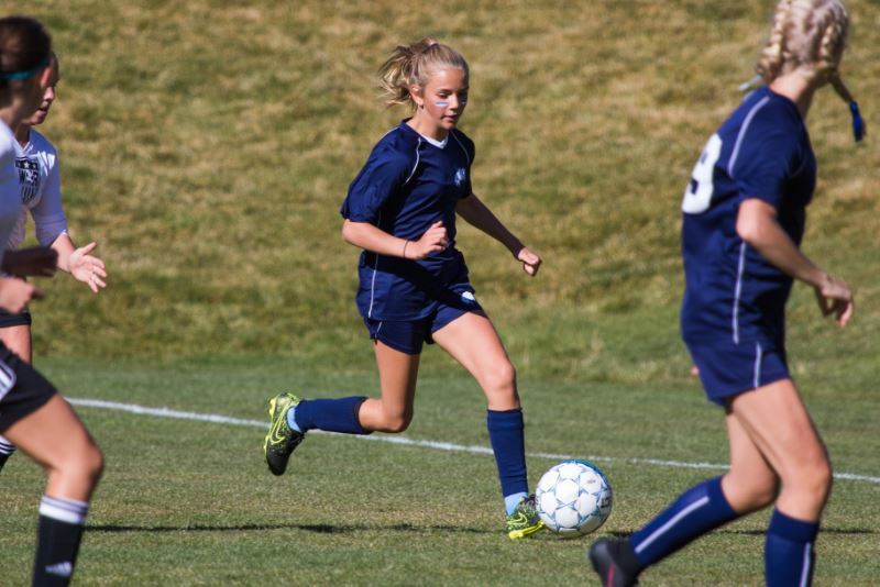 A girl dribbling a soccer ball during a soccer game