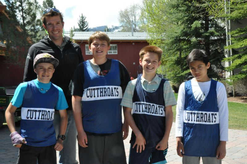 Four students outside in cutthroat pinnies