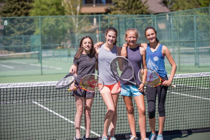 Four girls holding tennis rackets by the net of a tennis court