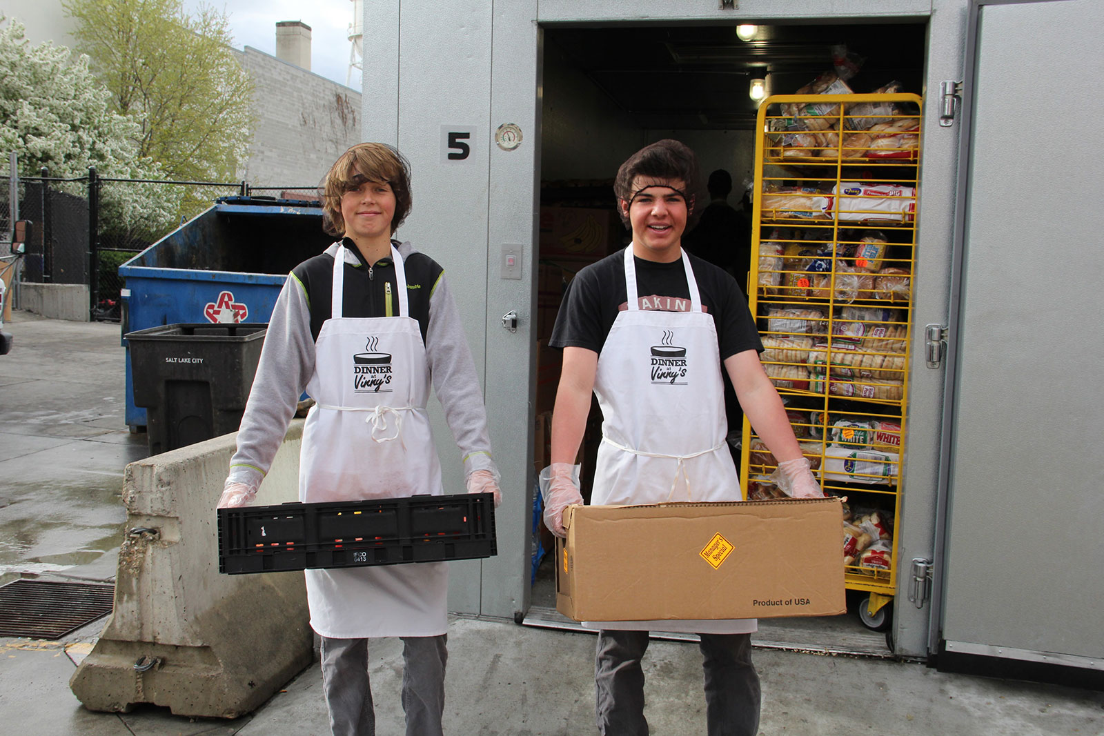 Two students in aprons carrying boxes