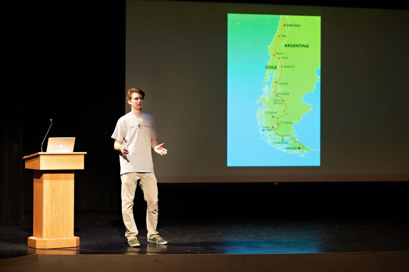 A student next to a podium presenting with an image of South America