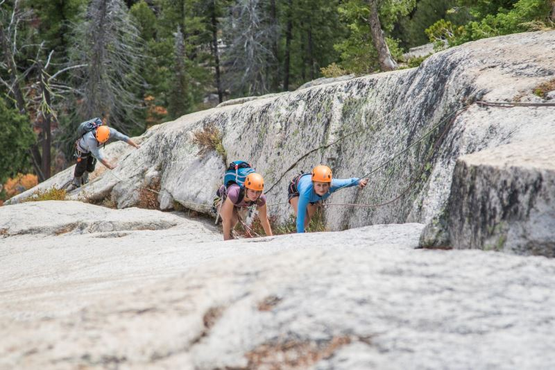 Three students climbing a rocky surface