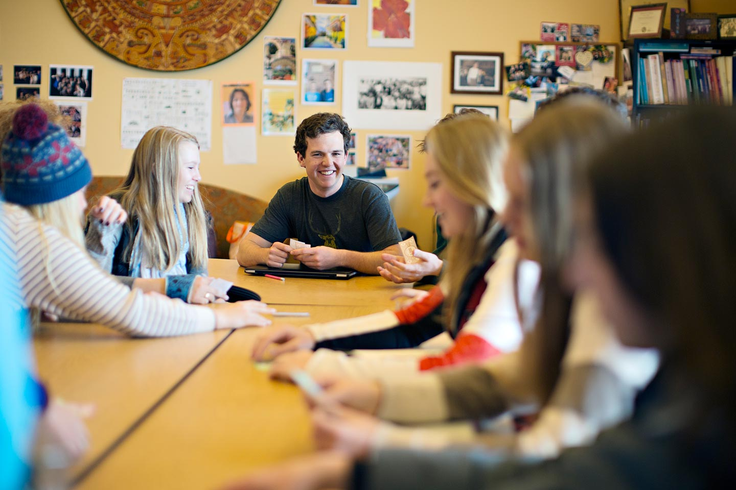 Students talking around a table in class
