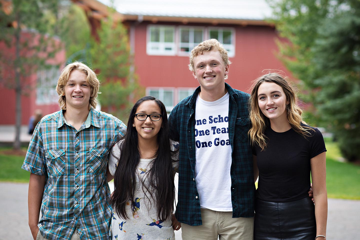Four students smiling in front of a red campus building